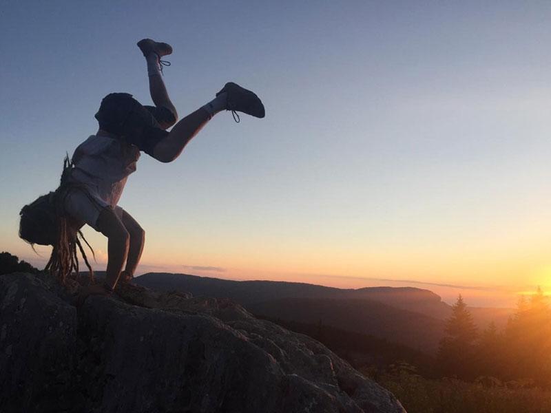 Enfant qui escalade un rocher la tête en bas
