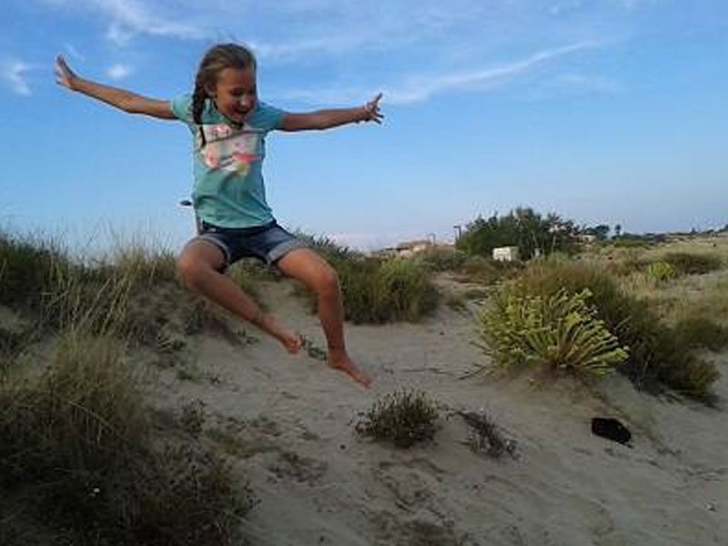 petite fille qui saute sur les dunes au bord de la mer