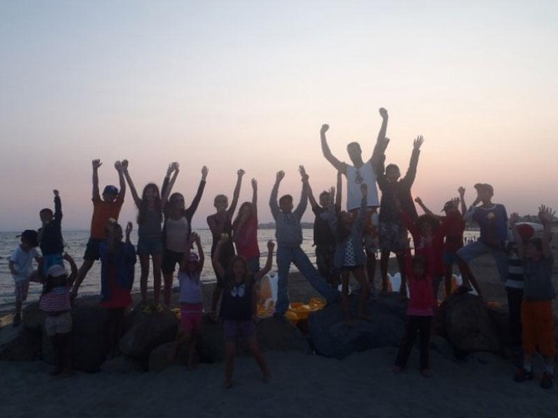 Groupe d'enfants en colonie devant le couché de soleil