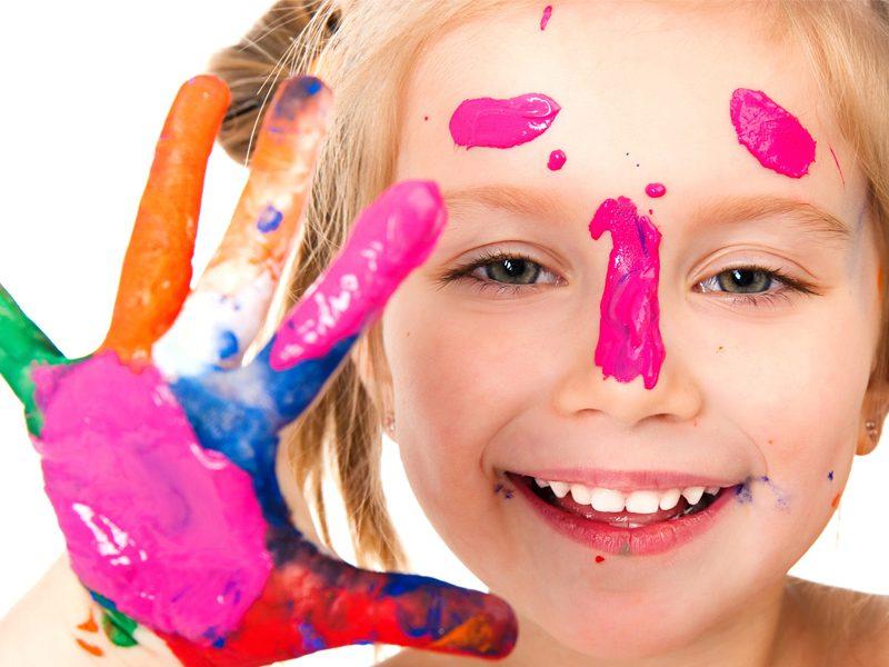 Portrait d'une fillette avec de la peinture sur les mains en colonie de vacances artistique été