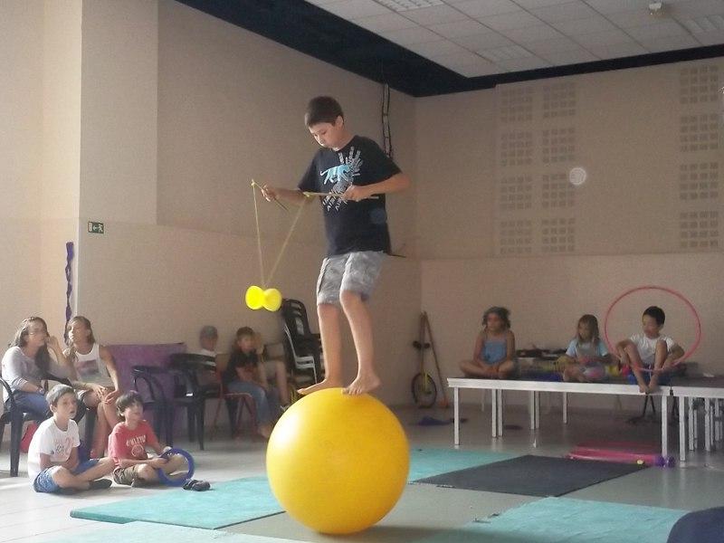 Enfant pratiquant le diabolo sur un ballon de cirque en colonie de vacances artistique