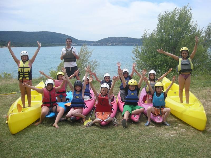 Groupe d'enfants au bord de l'eau faisant du canoe kayak en colonie de vacances