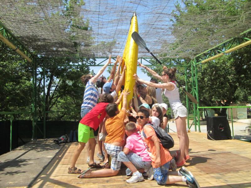 Groupe d'enfants en colonie de vacances posant devant un canoe kayak
