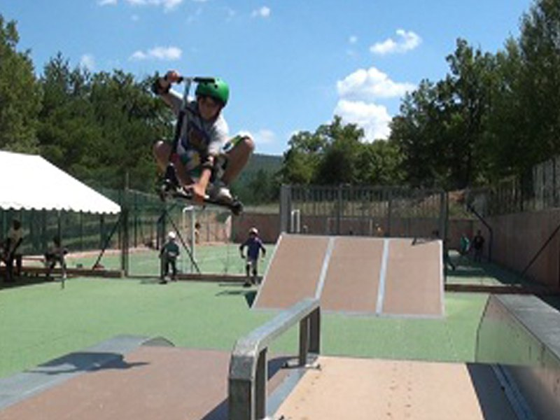 Enfants faisant de la trottinette sur un skatepark en colonie de vacances d'été