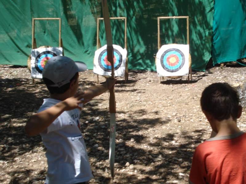 Trois enfants faisant du tir à l'arc en colonie de vacances multiactivités