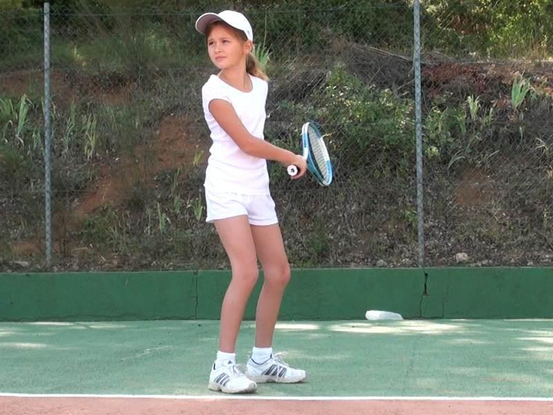 Fillette de 8 ans jouant au tennis en colonie de vacances d'été multiactivités