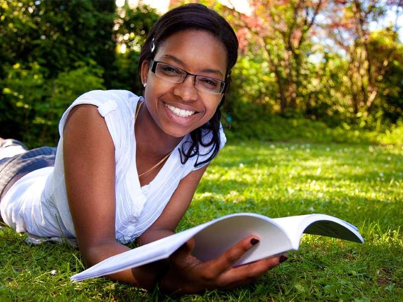 Jeune fille souriante lisant un livre