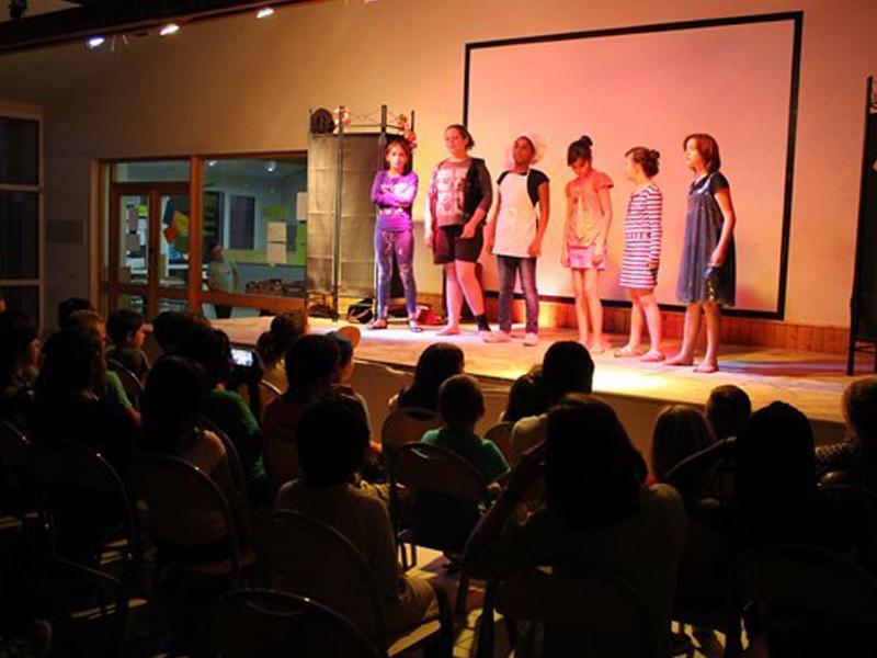 Enfants jouant une pièce de théâtre sur scène en colo
