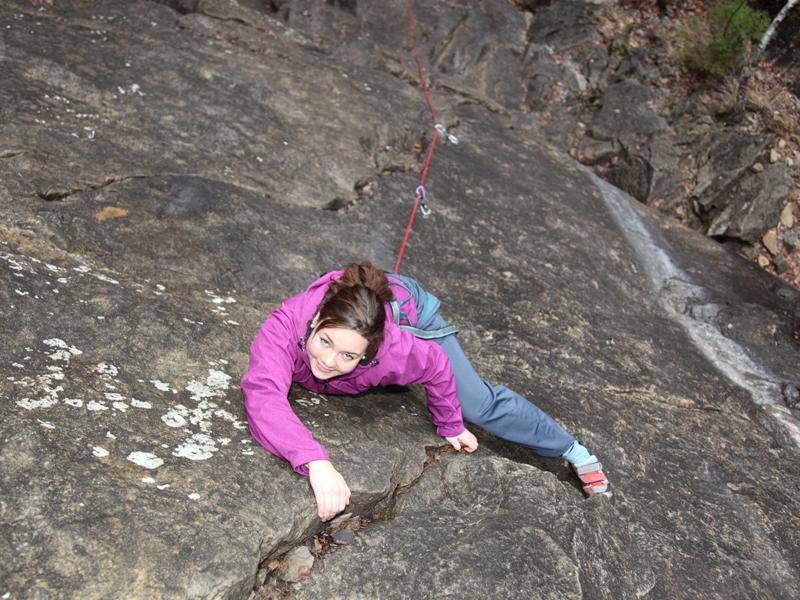 Adolescente sur le mur naturel d'escalade en colonie de vacances