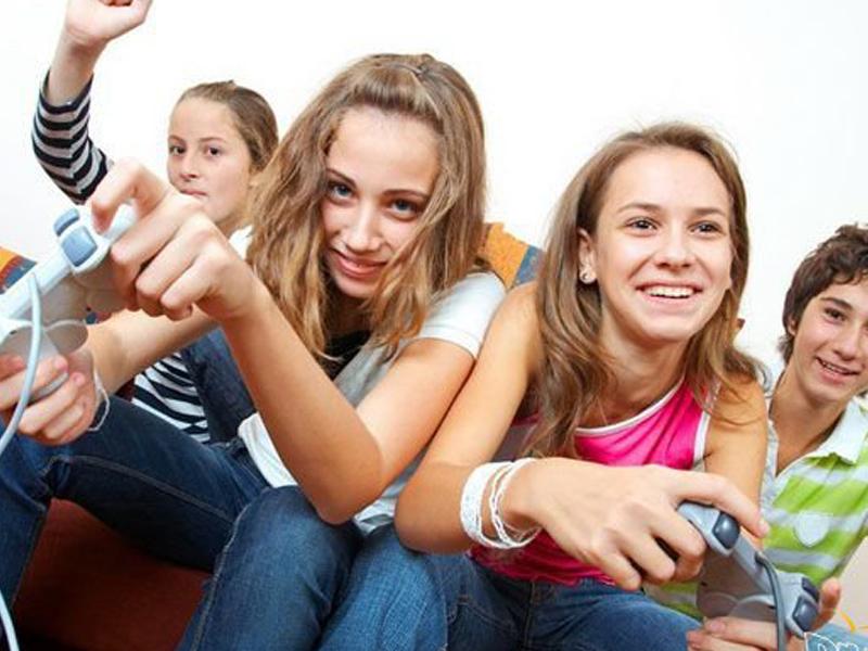 Groupe de jeunes jouant à la console en colonie de vacances