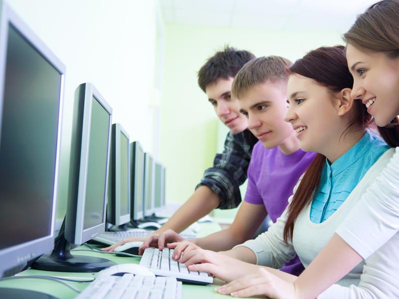 Groupe d'adolescents jouant aux jeux videos sur ordinateur