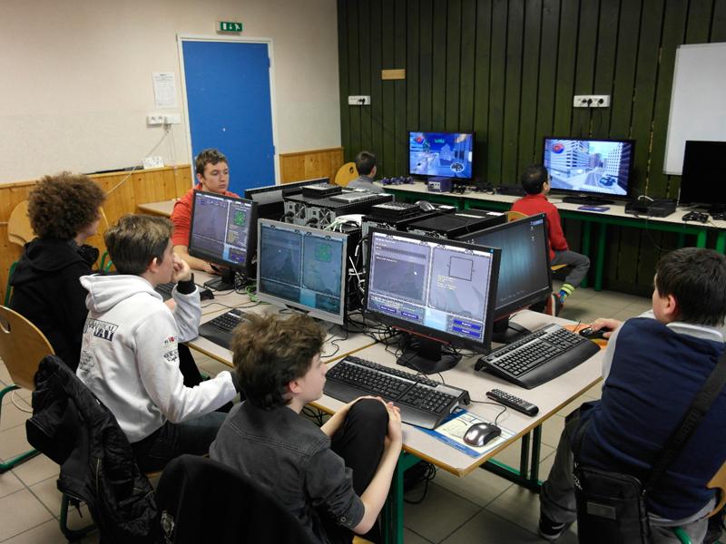 Groupe d'enfants jouant aux jeux vidéo en réseaux en colonie de vacances