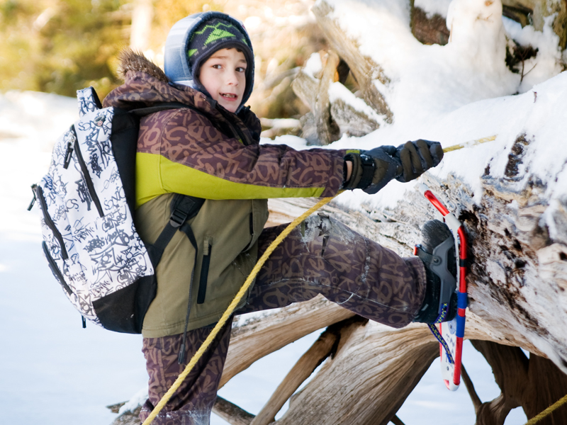 Enfant qui chausse ses raquettes à neige en colo