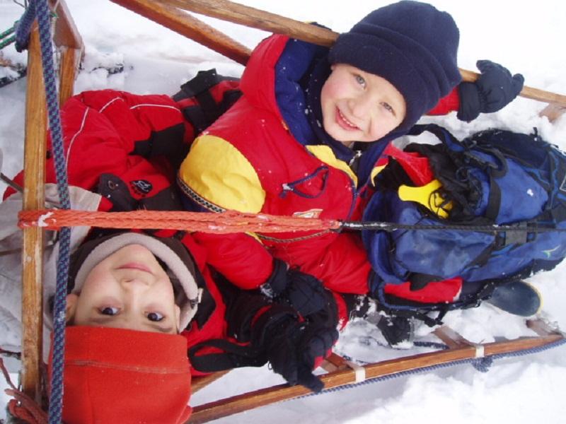Enfants dans un traineaux à chiens en colonie de vacances