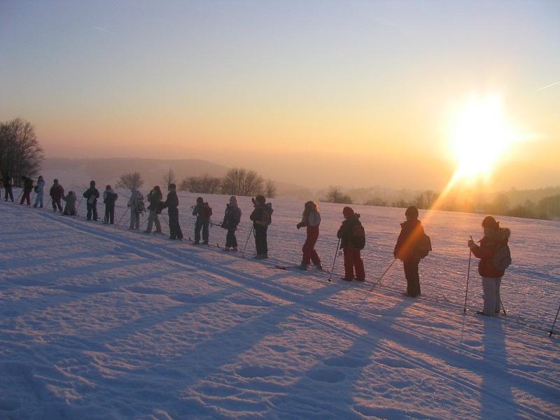 Enfants faisant du ski de fond sous un coucher de soleil en colonie de vacances