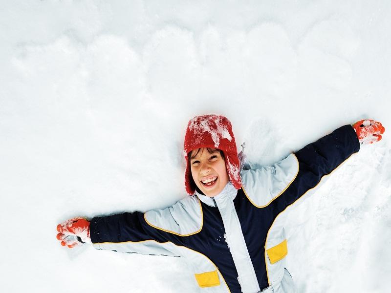 Enfant allongé dans la neige en colonie de vacances