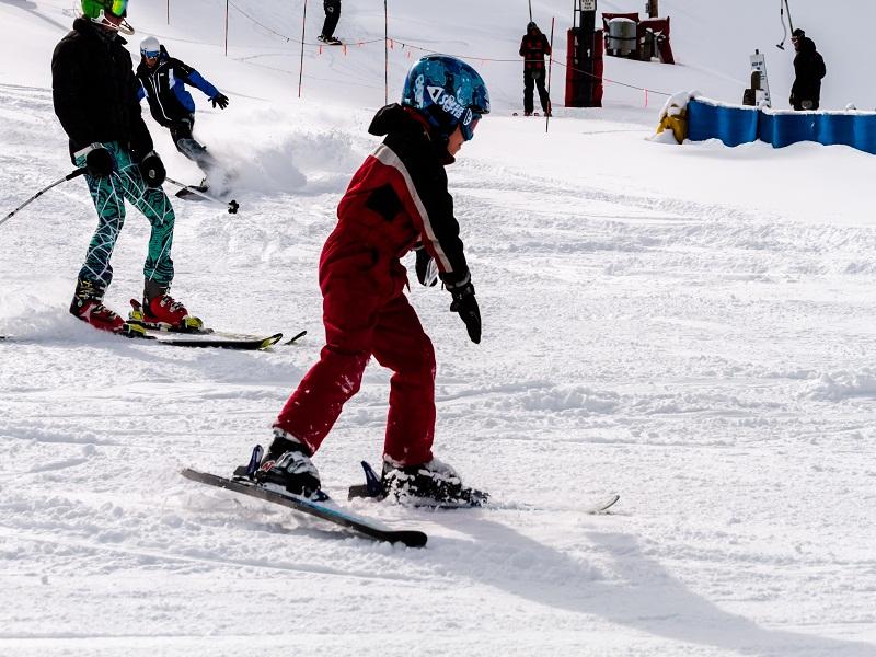Enfant apprenant à skier à la montagne en colonie de vacances