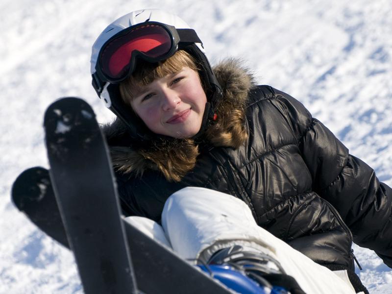 Enfant dans la neige avec ses skis en colonie de vacances