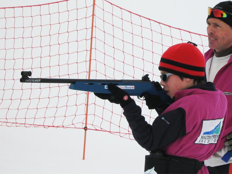 Enfant apprenant le tir de précision en biathlon d'hiver