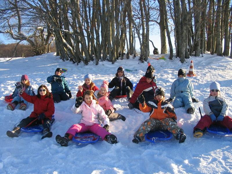 Groupe d'enfants faisant de la luge en colonie de vacances