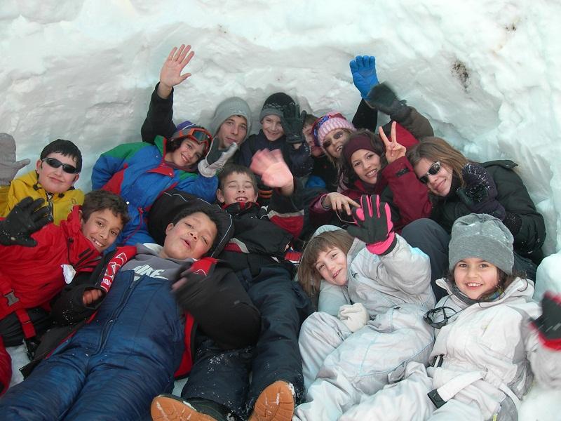 Groupe d'enfants à l'intérieur d'un igloo construit en colonie de vacances