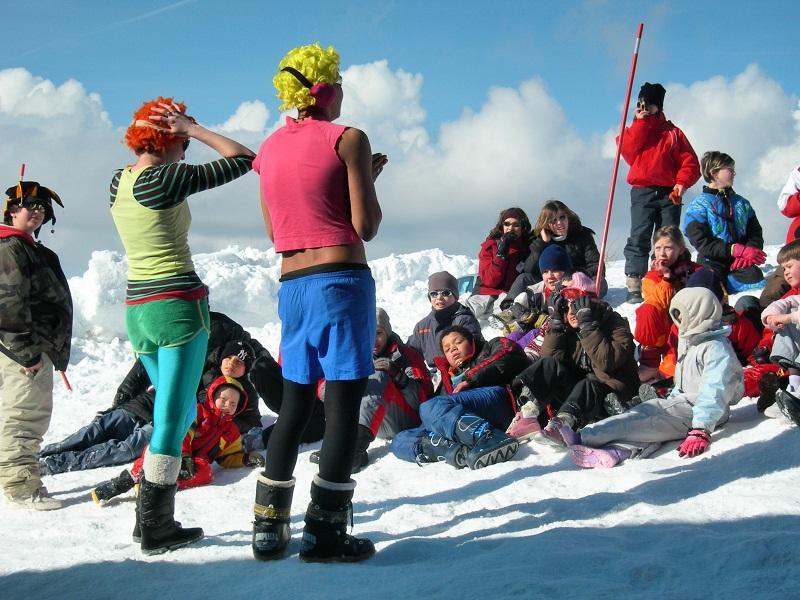 Animateurs de colonies de vacances déguisés et enfants sur les pistes de ski
