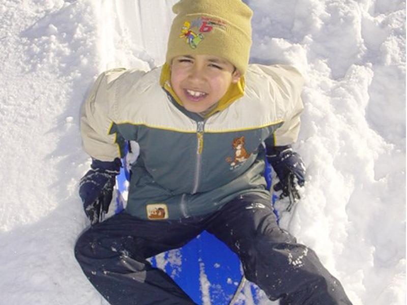 Portrait d'un enfant assis dans la neige