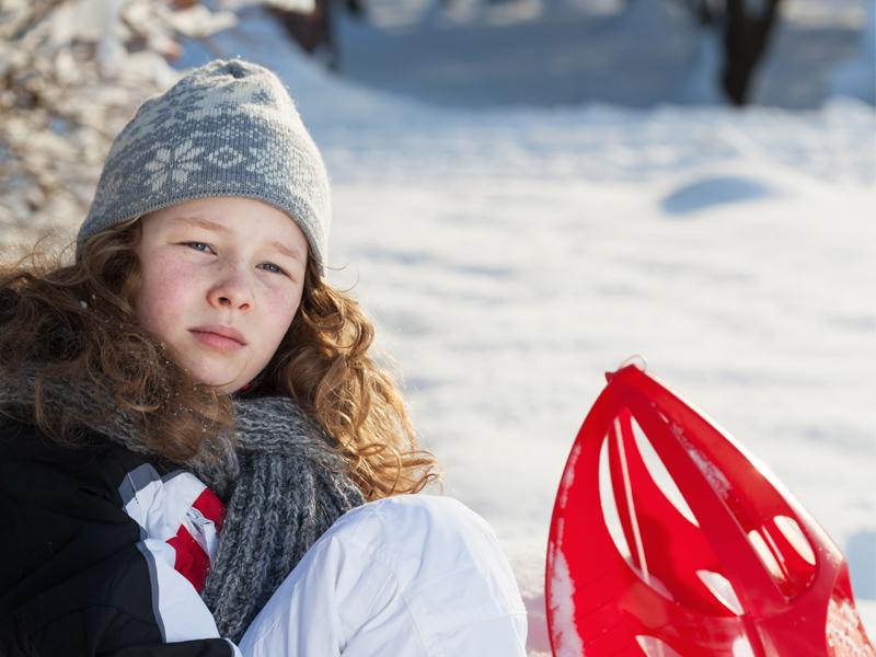 Fillette assise dans la neige avec ses raquettes à neige