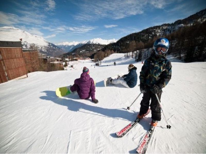 Enfants apprenant à faire du ski et du snowboard