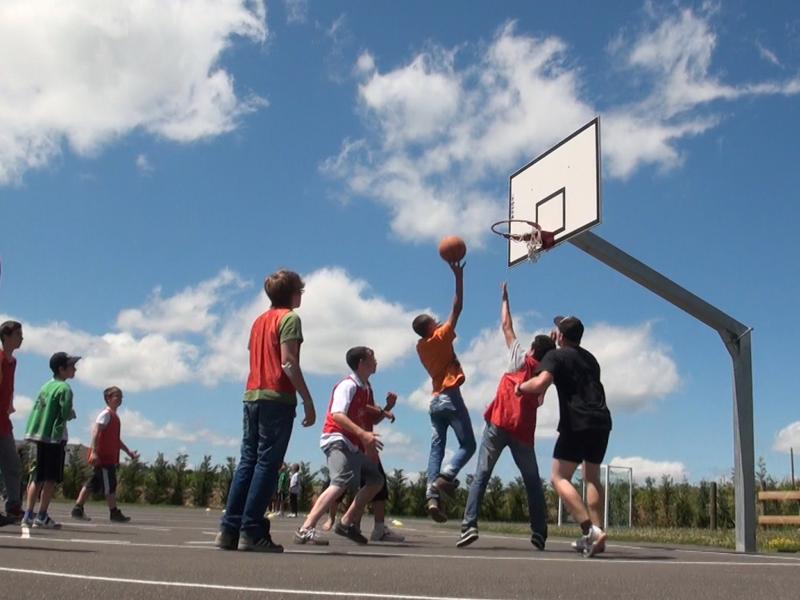 Adolescents jouant au basketball sur un terrain extérieur