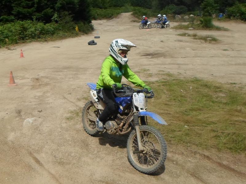 Enfant faisant de la moto sur un terrain de moto cross en colo