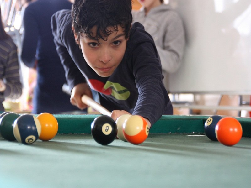 Adolescent jouant au billard temps libre en colo