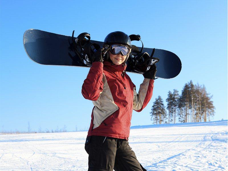 Enfant avec sa planche de snow à la montagne