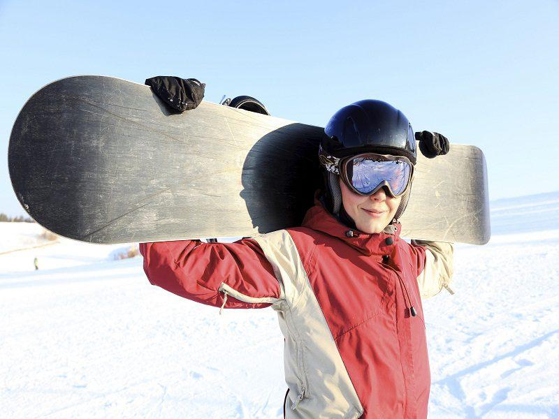 Ado portant un snowboard en colonie de vacances au ski