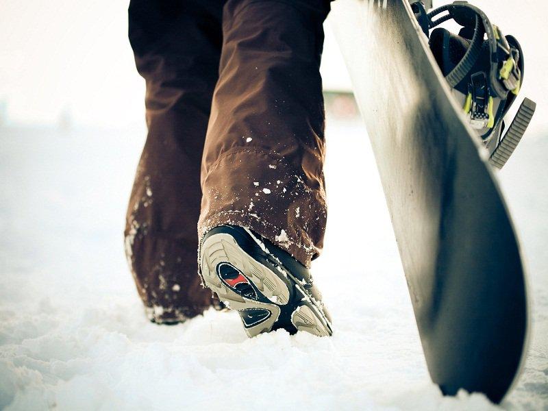 ado avec sa planche de snowboard en colo à la montagne