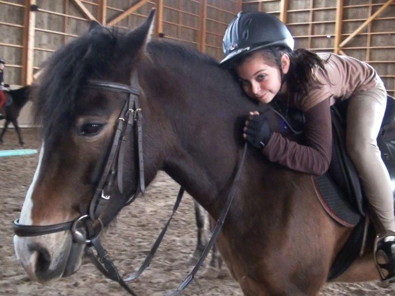 Fillette allongée sur son cheval en colonie de vacances