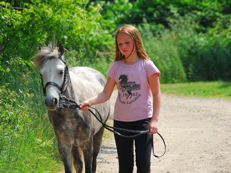 Fille en balade avec son cheval en colonie de vacances