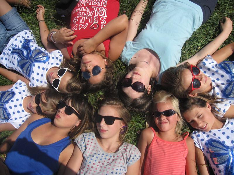 Groupe d'enfants allongés dans l'herbe en colonie de vacances