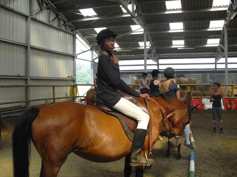Adolescents à cheval en manège en colo
