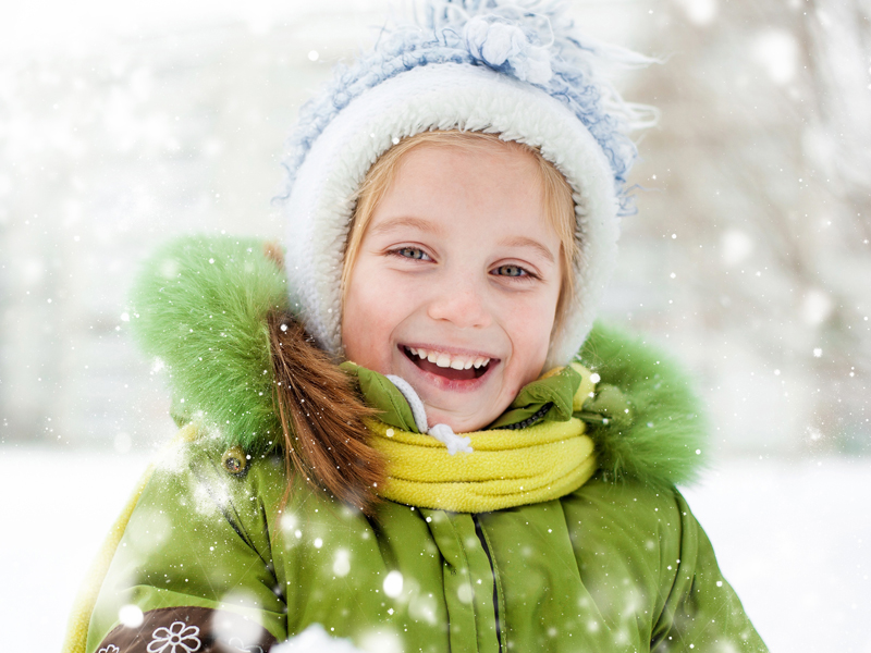 Petite fille blonde souriante sous la neige