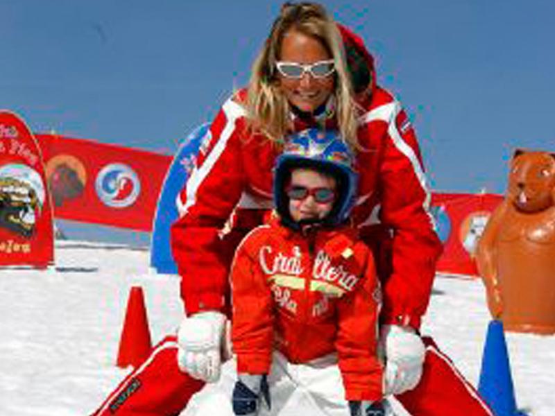 Monitrice de ski avec un enfant dans la neige