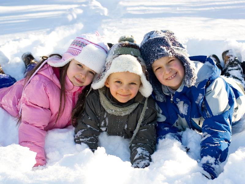 Trois jeunes enfants couchés dans la neige et souriants