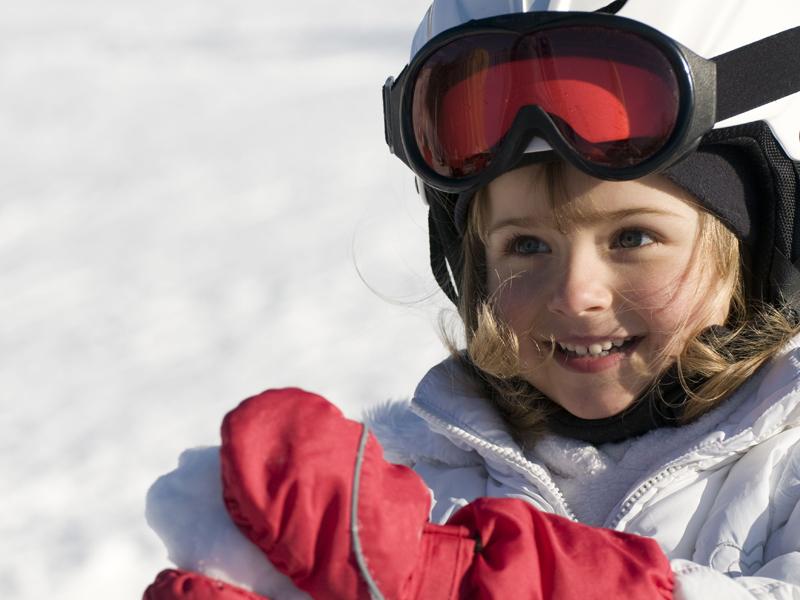 Petite fille à la neige en train de faire une boule de neige