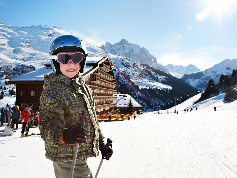 Garconnet devant un chalet à la montage sur les pistes de ski