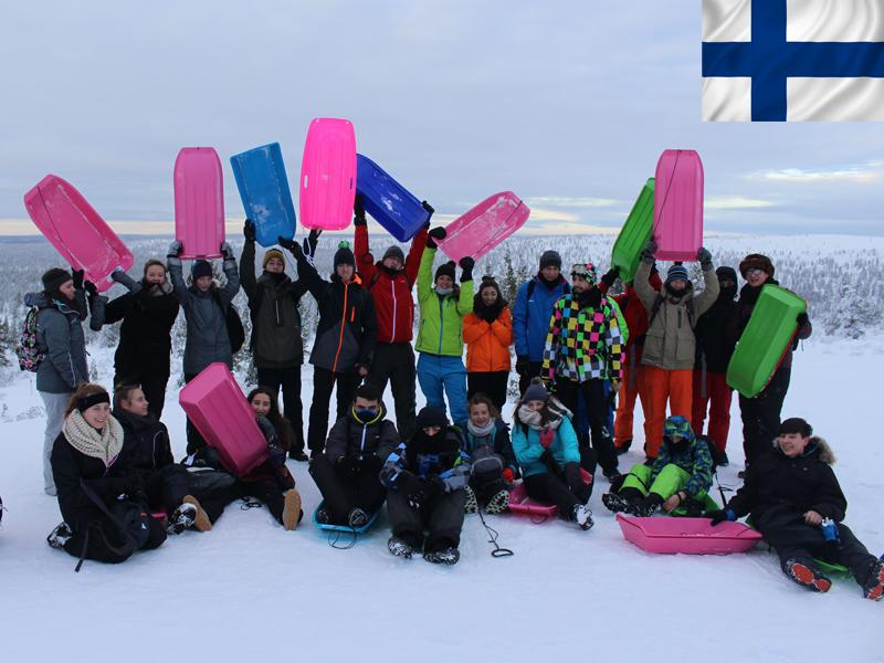 Groupe de jeunes en colonie de vacances en luge en Laponie