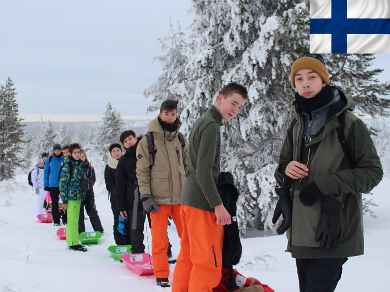 Groupe d'adolescents en colonie de vacances en Laponie en luge