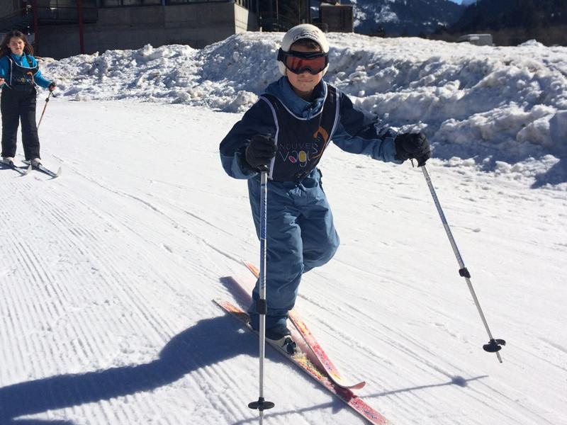 Enfant sur les pistes pratiquant le ski de fond en colonie de vacances de février