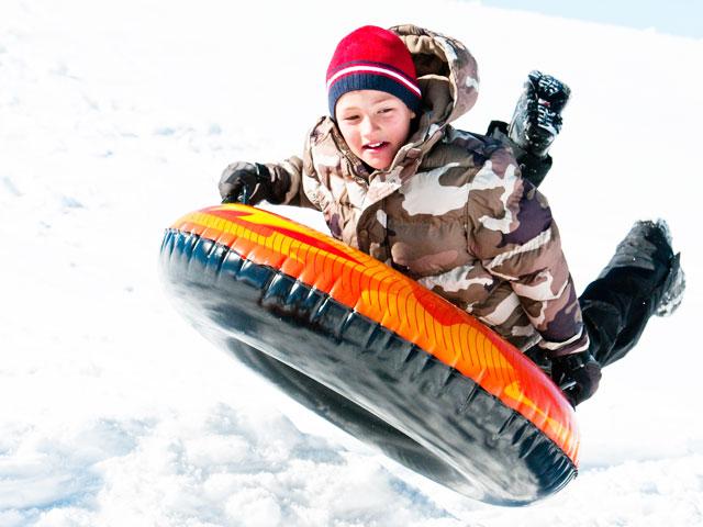 Enfants qui fait de la luge gonflable en colonie de vacances