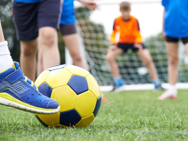 Enfant jouant au football en colonie de vacances sportive