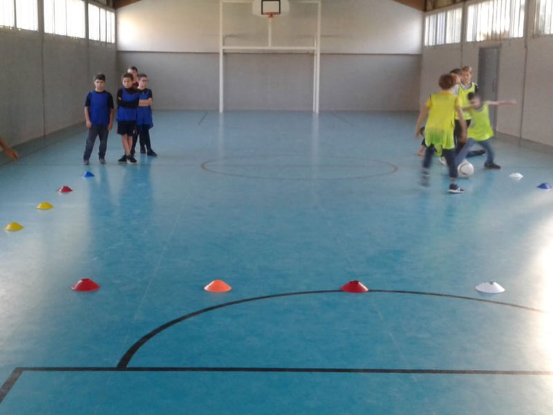 Enfants pratiquant le football en colonie de vacances sen gymnase